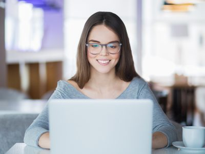 Portrait of cheerful Caucasian female student wearing eyeglasses using laptop in cafe for studies or networking and smiling